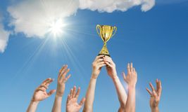 Winning team is holding trophy in hands. Many hands against blue sky stock photo