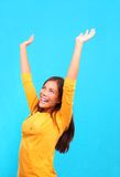 Winning woman cheering. Successful woman raising her hands up in the air in hapiness on a colorful background Stock Images