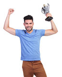 Winning young casual man with a big trophy cup. And hands in the air Royalty Free Stock Image