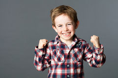 Winning young child with tooth missing raising arms for excitement. Winning kid - winning young red hair child with a tooth missing raising his arms for Stock Photos