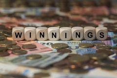 Winnings - cube with letters, money sector terms - sign with wooden cubes Stock Photos