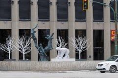 WINNIPEG, CANADA - 2014-11-17 : La sculpture en enfants d'arbre par Leo Mol a entouré par des décorations d'hiver devant Photographie stock libre de droits