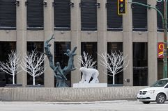 WINNIPEG, CANADA - 2014-11-17: Tree Children sculpture by Leo Mol surrounded by winter decorations in front of the. Richardson Building on Portage ave in the royalty free stock photography