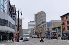 Winnipeg, Manitoba, Canadá - 2014-11-17: Uma pessoa em uma cadeira de rodas que cruza a interseção da avenida de Portage e do st  Foto de Stock Royalty Free
