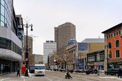 Winnipeg, Manitoba, Kanada - 2014-11-17: Osoba krzyżuje skrzyżowanie Portage ave i Smith st w wózku inwalidzkim zdjęcia royalty free