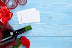 Wino i prezent na błękitnym drewnianym tle Zdjęcia Royalty Free