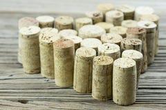 Wino korki tworzą kierowego kształta wizerunek na drewnianym stołowym tle Obrazy Stock