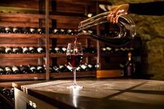 Wino wypełnia szkło Ręki mienie obliczająca butelka wino Wino sklepieniowa lokacja Obrazy Royalty Free