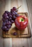 Winogrona i jabłko na drewnianej desce Obrazy Royalty Free