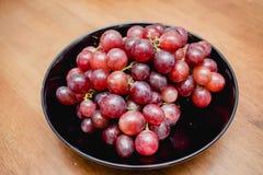 Winogrona w czarnym talerzu Zdjęcia Stock
