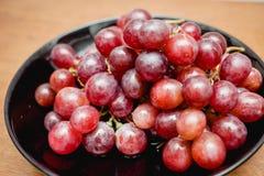 Winogrona w czarnym talerzu Obraz Stock