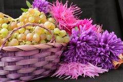 Winogrona w koszu i kwiatów asterach obrazy royalty free