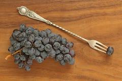 Winogrona Wiązka zmrok, czarni winogron kłamstwa na, drewnianej desce w górę i rocznika rozwidleniu obraz royalty free