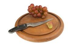 winogrono czerwony plasterek z nożem na drewnianej ciapanie desce zdjęcia royalty free