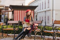 Winsome caucasian woman in knee high shoes sitting in park with city map. Romantic young lady with long hairstyle