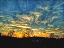 A Winter Sunset. Orange fades to blue in a sky spattered with clouds above silhouettes of trees Stock Images
