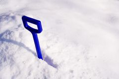 Winter. Bright blue plastic shovel in white snow Stock Image