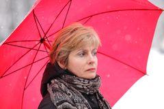 Winter. Woman with red umbrella in a winter day while snowing Stock Images