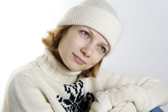 Winter. Portrait of the young woman in a woollen sweater, a cap, gloves; looks aside, blue eyes and red hair Royalty Free Stock Image