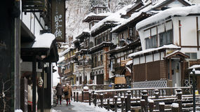 Winter. Two people taking a stroll along a path in wintertime in Ginzan Onsen, a town in Northern Honshu island, Japan stock photo