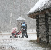 Winter. Couple with perambulator walking to park in the snow Royalty Free Stock Images