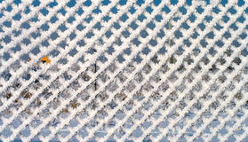 Winter abstraction. Background from a metal wire mesh fence covered with snow Stock Photography