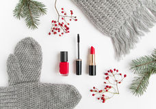 Winter accessories collage with cosmetics and clothes on white background. Flat lay, top view. Winter accessories collage with cosmetics, woolen scarf and Stock Photo