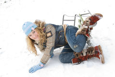Winter acitvities. Young beautiful girl falling from sledge into the snow Stock Photos