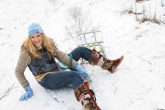 Winter acitvities. Young beautiful girl falling from sledge into the snow Stock Image