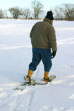 Winter activities. Man with snowshoes walking on snow during winter Stock Photos