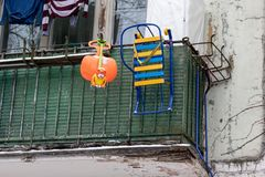Winter activities equipment, sledge, icicle and plastic toy hanging on a balcony railing royalty free stock images