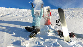Winter activities. Friends with snowboards throwing snow on the mount peak Stock Image