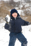 Winter activities II. Young boy throwing snowballs onwinter background Royalty Free Stock Photos