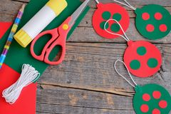 Red and green Christmas balls hanging, scissors, pencil, glue stick on an old wooden background with copy space for text royalty free stock images