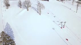 Winter activities skiing and snowboarding on snow slope aerial view. People on ski elevator in ski resort drone view. Winter vacation on luxury ski resort stock footage