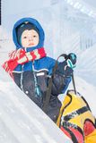 Happy boy toboggan from a snow slide on colorful tube royalty free stock image