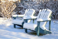 Winter Adirondack Chairs. Wooden Adirondack chairs covered in snow in a backyard garden Stock Photos
