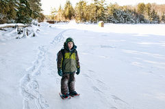 Winter adventure. Young boy out snow shoeing across a frozen lake Stock Photos