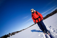 Winter Advture Skiing. A woman cross country skiing across a frozen lake Stock Images
