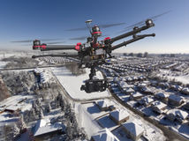 Winter Aerial Patrol. A drone with a camera and raised landing gears flying high above a residential area covered with fresh snow in a bright sunny winter day Stock Photo