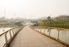 Winter afternoon sunlight on suburban planked footbridge over ri. Winter afternoon sunlight on suburban planked footbridge over the river,Chengdu,China royalty free stock images