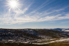 Winter Afternoon Sunshine in Lesotho. The shining sun begins to set on a winter afternoon above the treeline in a snowy remote area of Thaba-Tseka in Lesotho royalty free stock photos