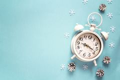 Winter alarm clock with pine cone and copy space on blue backgro. Und.  Christmas timer. Time to celebrate Royalty Free Stock Photo