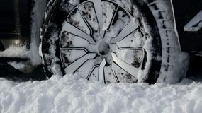 Winter all-terrain tire tread packed with snow stock photo. Wheel of SUV vehicle with winter all-terrain tire in the deep snow with tread packed with snow stock Stock Photos