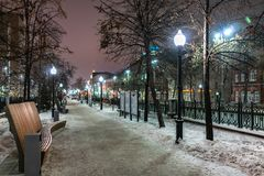 Winter alley in the heart of the city at night royalty free stock photography