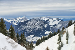 Winter Alpine landscape framed by firs forest slopes Stock Image