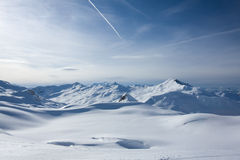 Winter Alpine landscape at sunset. Snowcovered mountain ridge. White traces of airplanes in the sky Stock Photography