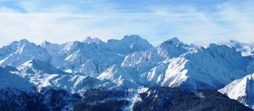 Winter alpine mountain range under a blue sky. Winter alpine mountain scene under a blue sky Royalty Free Stock Photos
