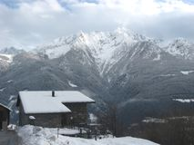 Winter alpine panorama. A small mountain house under the snow. Italian Alps, winter 2008 Royalty Free Stock Photography