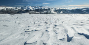 Winter alpine scenery with snow dunes and frozen snow Royalty Free Stock Images